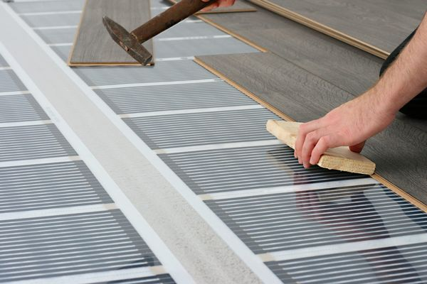 Man installing laminate floor over infrared carbon heating system